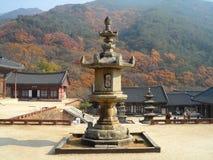 The largest stone lantern in South Korea against mountain range of fall foliage Stock Photos