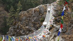 Porters Suspension Bridge Tourists Travel Nepal Himalayas Mountains 4k. Largest suspension bridge in Solu Khumbu valley with colorful prayer flags, trekking area stock video