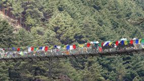 Suspension Bridge Porters Travel Nepal Himalayas Mountains 4k. Largest suspension bridge in Solu Khumbu valley with colorful prayer flags, trekking area to the stock footage