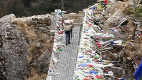 Porter Suspension Bridge Travel Nepal Himalayas Mountains 4k. Largest suspension bridge in Solu Khumbu valley with colorful prayer flags, trekking area to the stock video footage