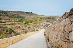 Largo camino abajo de la colina en la isla de Gozo Fotos de archivo libres de regalías
