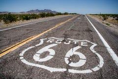 Largo camino con una insignia de la ruta 66 pintada en ella Foto de archivo