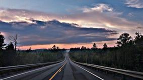 Largo camino durante una salida del sol de niebla Fotografía de archivo