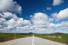 Largo camino a las colinas verdes. Fotos de archivo