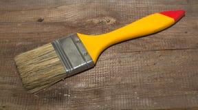 Largura da escova de pintura 2 polegadas com punho amarelo em um fundo de madeira foto de stock