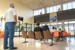 Passenger waiting hall at Larissa Train Station. Larissa, Greece - June 11th, 2018: Passengers sitting are looking the monitors at the waiting hall of the Stock Images