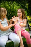 Larking children. Two small girls (sisters) larking in backyard sitting on bench Royalty Free Stock Image