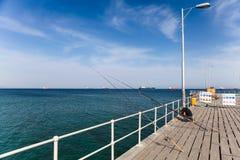 LARNACA, CHIPRE - 29 DE MAYO DE 2014: El pescador con las cañas de pescar está cogiendo pescados en el mar del embarcadero Fotos de archivo