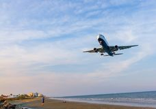 British Airways Boeing 767 over McKenzie beach before landing at stock photography