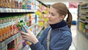 LARNACA, CYPRUS - FEBRUARY 1, 2017: Beautiful woman choosing packed juice in supermarket. stock footage