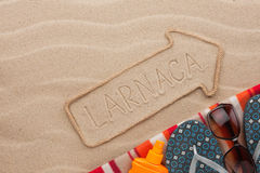 Larnaca  pointer and beach accessories lying on the sand Royalty Free Stock Photo