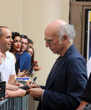 Larry David Signs A Playbill. Actor Larry David signs an autograph on a playbill of his Broadway show, Fish In The Dark, in the theater district in Manhattan, NY Royalty Free Stock Image