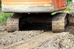 larver av grävskopan för crawlsimmare för tung konstruktionsutrustning på platsen för utvidgningen vägen arkivfoto