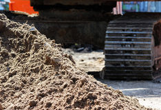 larvgrävskopa och en hög av sand på byggnadskonstruktionsplatsen som reparerar vägen Arkivfoto