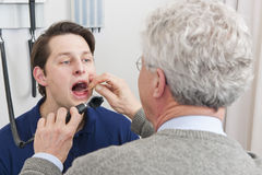 Laryngitis. General practitioner examining mouth and throat of a patient with laryngitis Stock Images