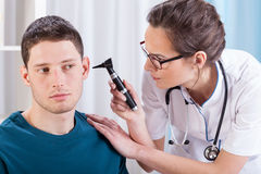 Laryngologist examining patient ears. Young laryngologist examining patient by professional otoscope Royalty Free Stock Photos