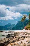Las小屋靠岸,棕榈树、山和cloudscape在El Nido,巴拉旺岛海岛,菲律宾 免版税库存照片