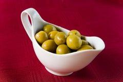 Las aceitunas verdes mienten en un barco de salsa blanco Imagen de archivo