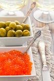 Las aceitunas y el caviar rojo están en dos cuencos blancos Foto de archivo libre de regalías