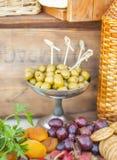 Las aceitunas y las frutas en un vintage adornaron maravillosamente la tabla Imágenes de archivo libres de regalías