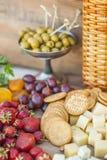 Las aceitunas y las frutas en un vintage adornaron maravillosamente la tabla Imagen de archivo