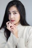 Las actitudes asiáticas de la muchacha manejan su barbilla Fotos de archivo
