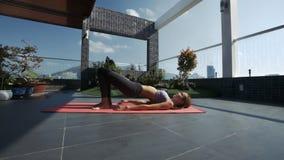 Las actitudes rubias de la yoga de los cambios de la muchacha en tejado gandulean