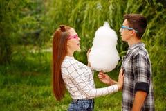 Las adolescencias cariñosas de los pares comen el caramelo de algodón Imagenes de archivo