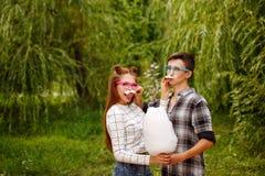 Las adolescencias de los amores comen algodón dulce Foto de archivo libre de regalías
