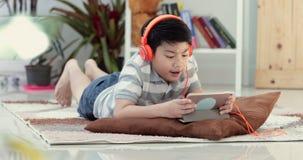 Las adolescencias del asiático pre se basan sobre piso y el jugar con la cara de la sonrisa tableta en casa almacen de metraje de vídeo
