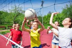 Las adolescencias emocionadas juegan cerca de red del voleibol en corte Foto de archivo libre de regalías