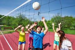 Las adolescencias en el movimiento con los brazos para arriba intentan coger la bola Fotografía de archivo libre de regalías