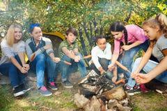 Las adolescencias en sitio para acampar asan a la parrilla las salchichas que se sientan cerca de la tienda Fotos de archivo libres de regalías