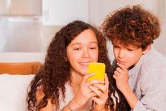 Las adolescencias felices con el teléfono celular mandan un SMS en red social Foto de archivo libre de regalías