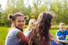 Las adolescencias internacionales felices se sientan juntas en prado Imagen de archivo