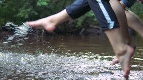 Las adolescencias se relajan por el río que se sienta al borde de un embarcadero de madera almacen de metraje de vídeo