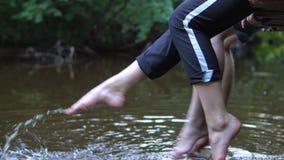 Las adolescencias se relajan por el río que se sienta al borde de un embarcadero de madera almacen de video