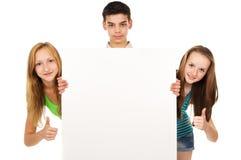 Las adolescencias sostienen un cartel Fotografía de archivo libre de regalías