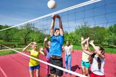 Las adolescencias todas están con los brazos encima del voleibol del juego Fotografía de archivo libre de regalías