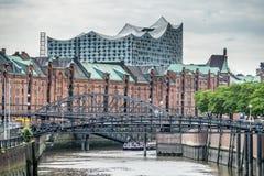 Las aduanas canalizan en el distrito viejo Speicherstadt del almacén en Hamburgo, Alemania con la sala de conciertos de Elbphilha Imagen de archivo