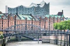 Las aduanas canalizan en el distrito viejo Speicherstadt del almacén en Hamburgo, Alemania con la sala de conciertos de Elbphilha Fotografía de archivo