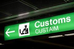 Las aduanas firman adentro el aeropuerto y la flecha de la dirección Imagen de archivo libre de regalías