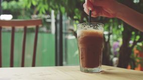 Las agitaciones de la muchacha helaron el café Bebida fría en la tabla almacen de metraje de vídeo