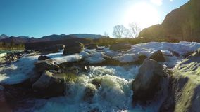 Las aguas de manatial en la corriente, la nieve mienten en el valle, el sol están brillando metrajes