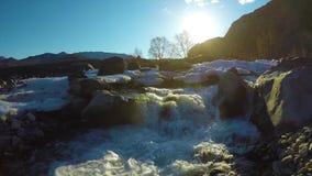 Las aguas de manatial en la corriente, la nieve mienten en el valle, el sol están brillando almacen de metraje de vídeo