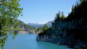 Las aguas de un lago alpino fluyen tranquilamente en los bancos del lago almacen de video