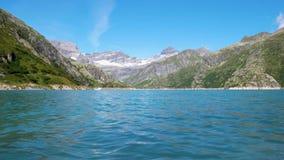 Las aguas de un lago alpino fluyen tranquilamente en los bancos del lago metrajes