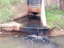 Las aguas residuales de las casas descargadas adentro al río Fotos de archivo libres de regalías