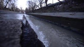 Las aguas residuales drenan en la alcantarilla de la ciudad plan grande y medio almacen de metraje de vídeo