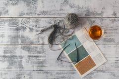 Las agujas que hacen punto y el hilado en fondo de madera/lanas naturales hacen punto Imagenes de archivo